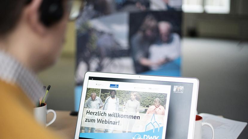 Ein Mann sitzt vor einem Bildschirm, auf dem eine virtuelle Veranstaltung stattfindet.