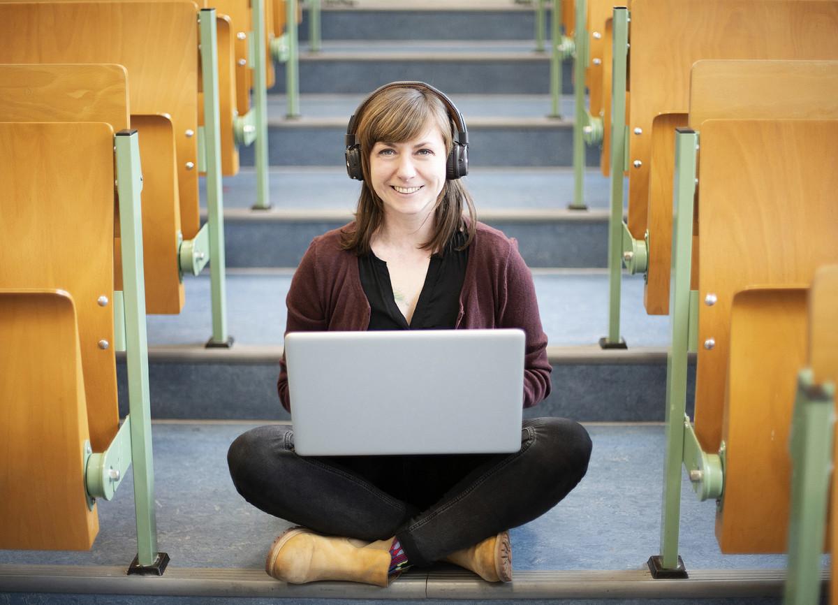 Junge Frau mit Laptop auf den Knien