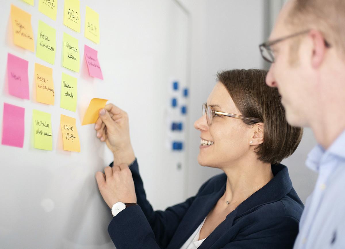 Eine Frau und ein Mann stehen vor einer Pinnwand. Die Frau klebt lächelnd bunte Zetteln mit Notizen darauf.