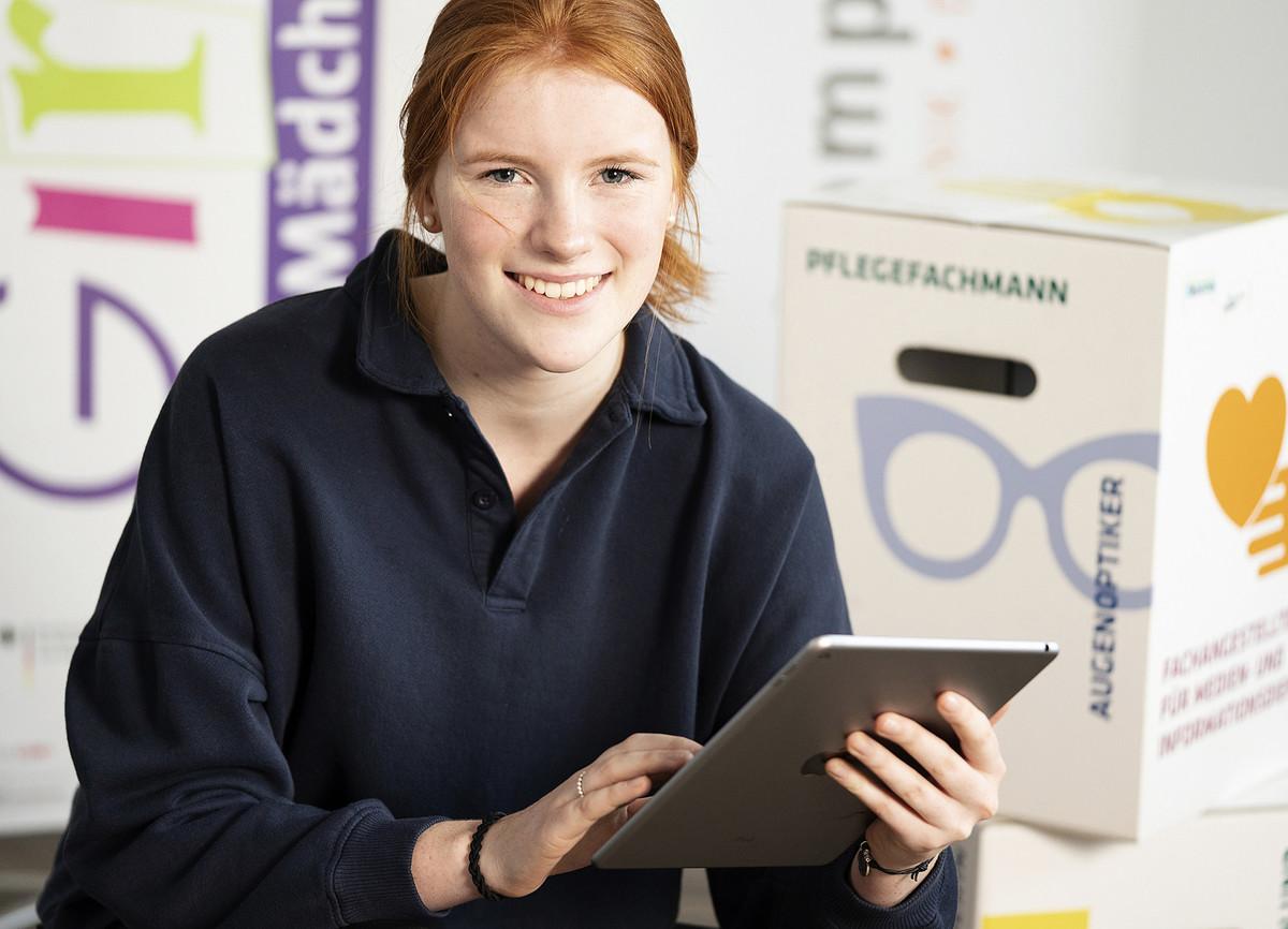 """Ein Mädchen sitzt an einem Tablet und lächelt in die Kamera. Im Hintergrund ist ein Aufsteller mit dem Schriftzug """"Girls'Day"""" zu sehen."""