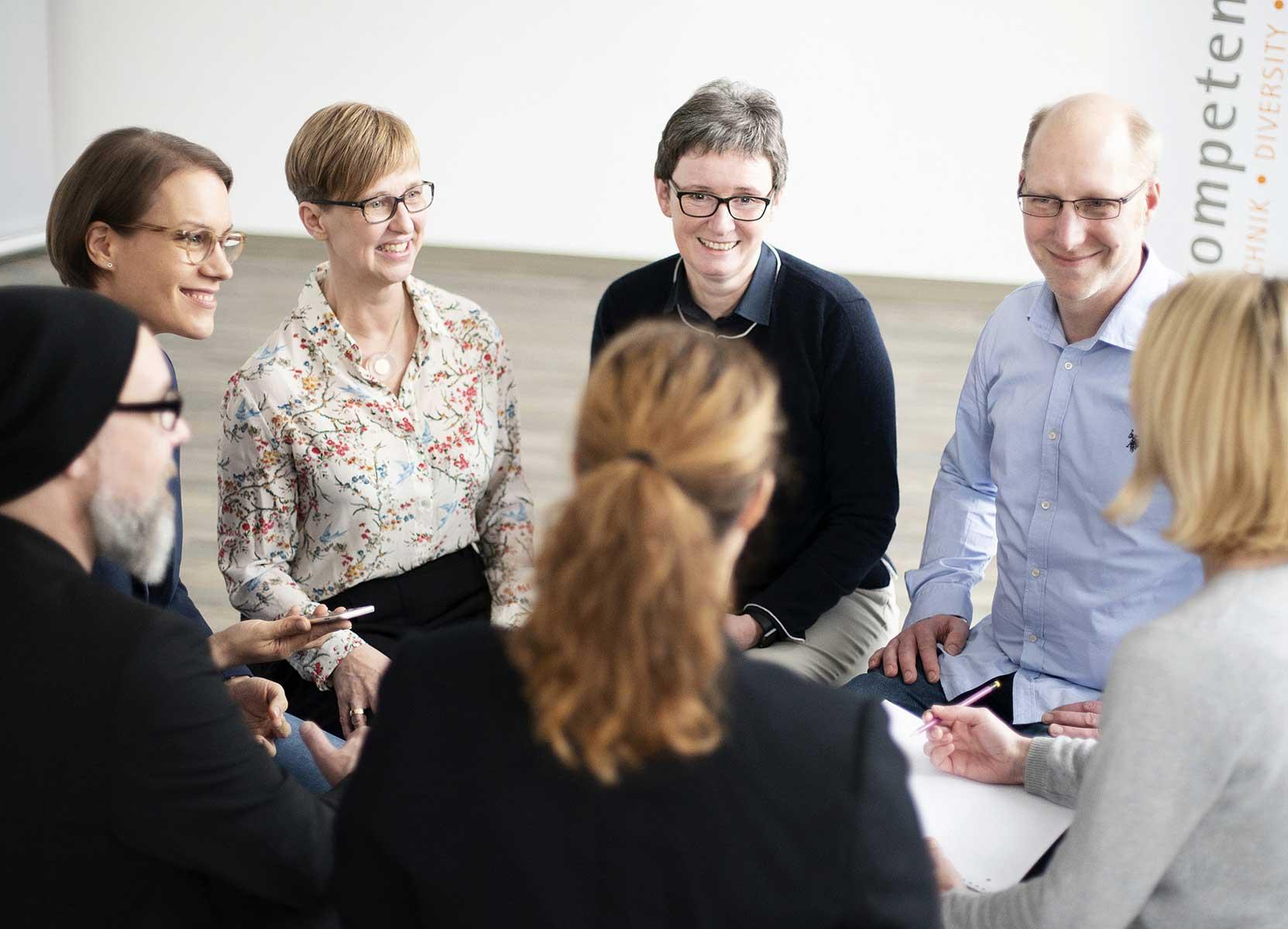 Sieben Personen sitzen im Kreis und sprechen