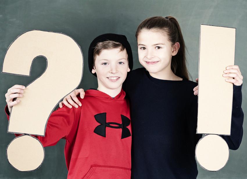 Junge und Mädchen mit Fragezeichen und Ausrufezeichen