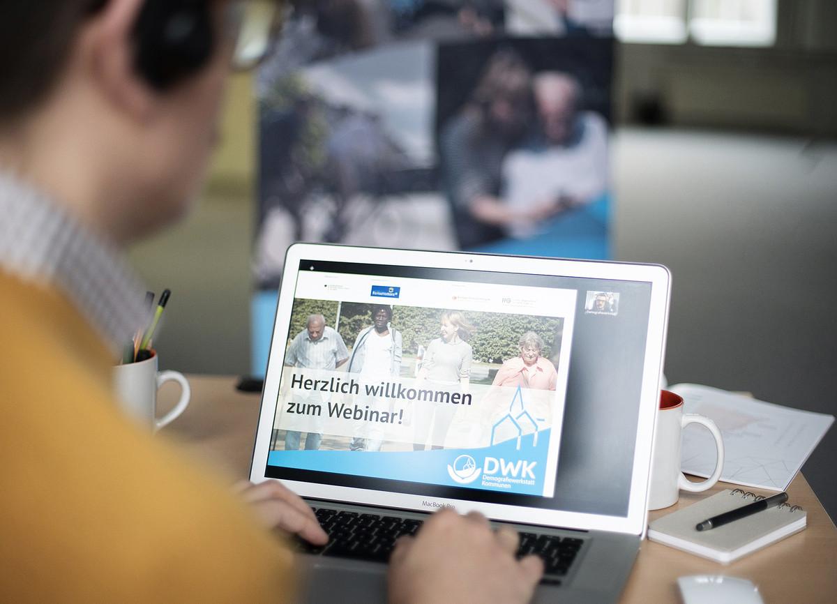 Ein Mann sitzt mit einem Headset vor einem Bildschirm, auf dem ein Seminar der Demografiewerkstatt Kommunen läuft.
