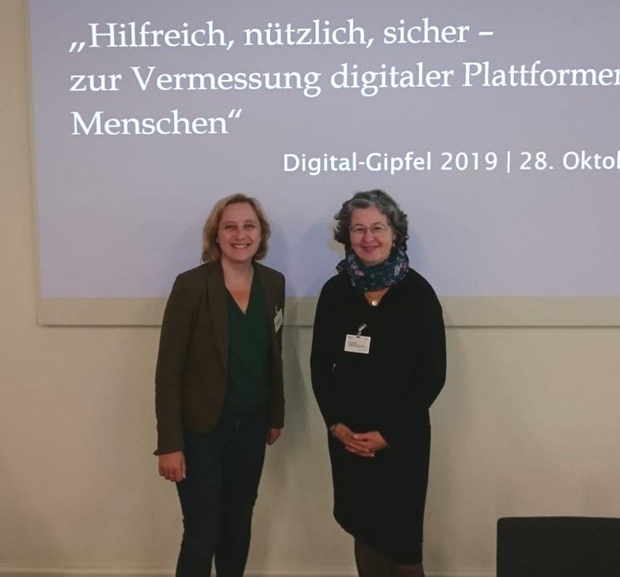 Zwei Frauen stehen vor Wand mit Präsentation