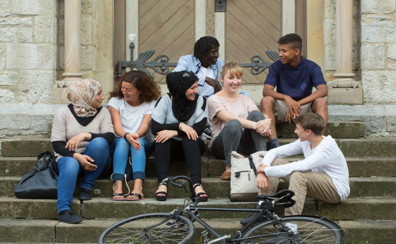 Eine Gruppe Menschen unterschiedlichen Aussehens sitzt auf einer Treppe