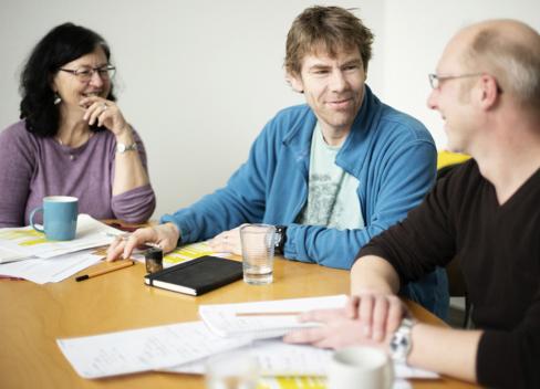 Technik-Team kompetenzz: 3 Personen sitzen am Tisch