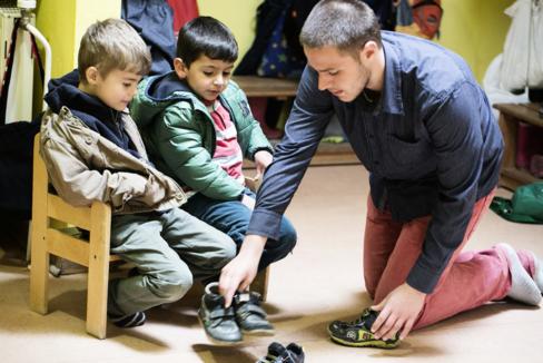 Ein junger Mann hilft zwei Jungen im Kindergartenalter beim Schuhe anziehen.