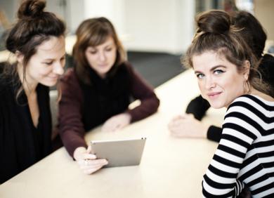 Vier Frauen sitzen an einem Tisch und schauen auf ein Tablet. Eine Frau schaut in die Kamera.