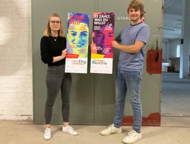 Junger Mann und junge Frau mit Plakaten